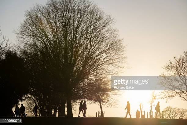 South Londoners out for a late-afternoon walk, enjoy the last sunlight during the second lockdown of the Cornavirus pandemic, in Brockwell Park, on...