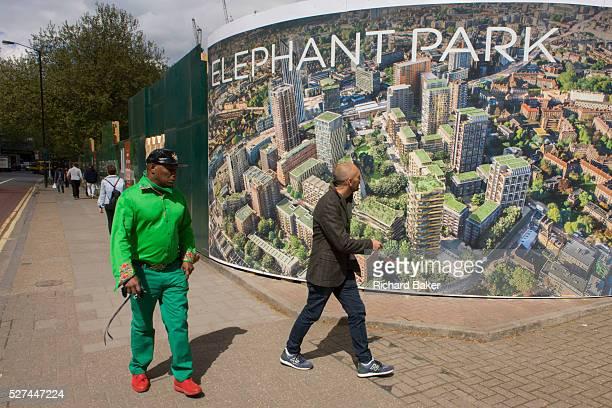 South Londoners walk past a regeneration project hoarding image at Elephant Park at Elephant Castle London borough of Southwark Southwark Council's...