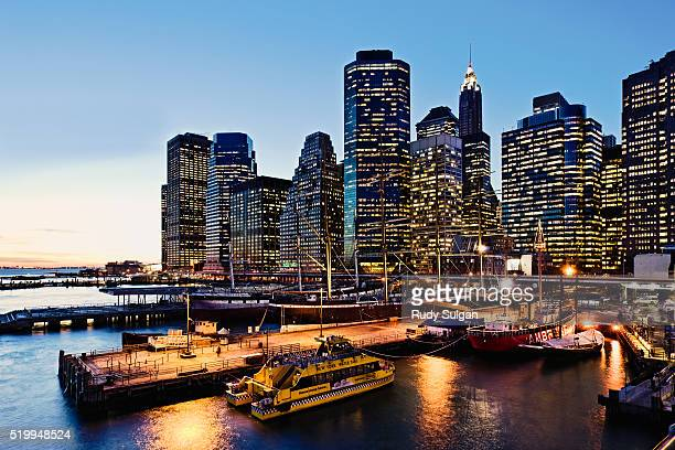 south street seaport and lower manhattan skyline at dusk - south street seaport stock photos and pictures