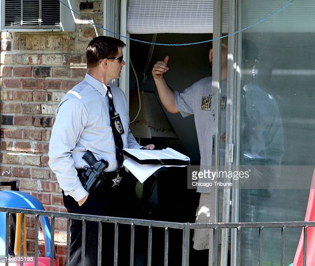South Suburban Major Crimes Task Force investigators talk to neighbors next to the apartment building where Estrella Carrera was found stabbed to...