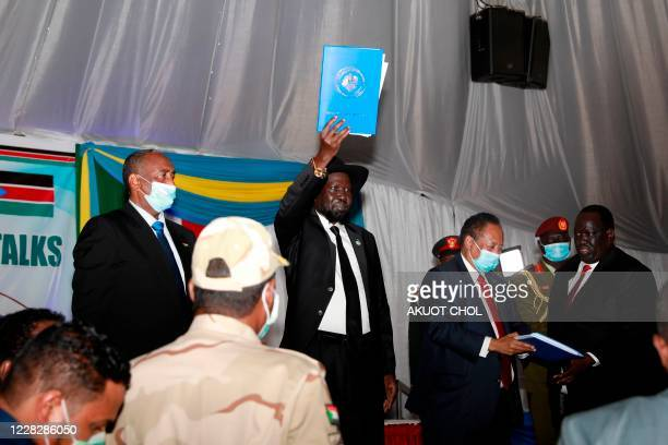 South Sudan President Salva Kiir holds up the document of the signing between the rebel groups and the government during the singing of the Sudan...