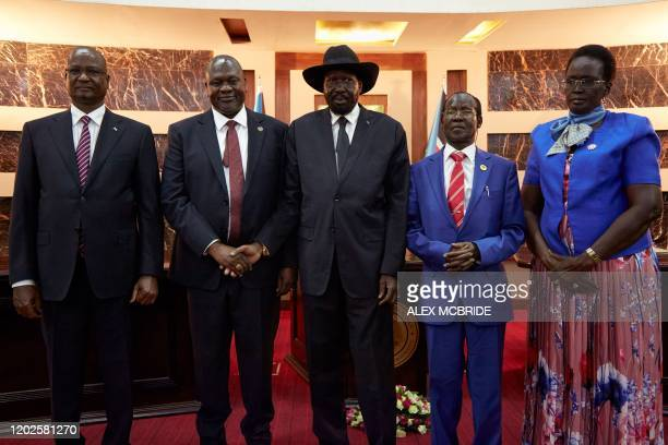 South Sudanes President Salva Kiir shakes hands with First Vice President Dr Riek Machar as Third Vice President Taban Deng Gai Second Vice President...