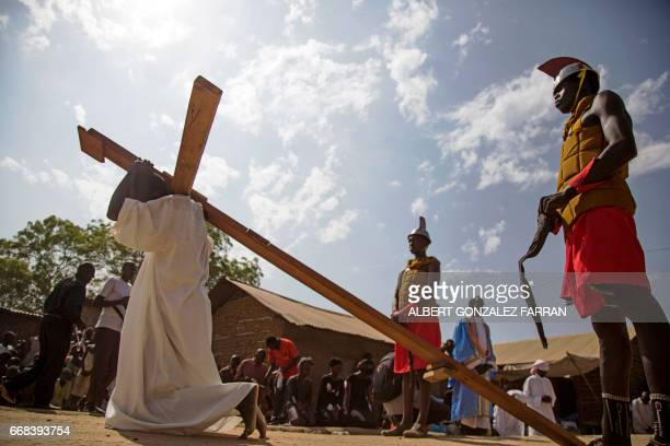TOPSHOT South Sudanese actor Emmanuel Aban as a Jesus Christ carries the cross during the Good Friday procession ahead of Easter in Juba South Sudan...