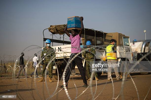 A South Sudanese boy carries a box of water bottles at the Tongping United Nations Mission in South Sudan base in Juba on January 17 2014 Every...