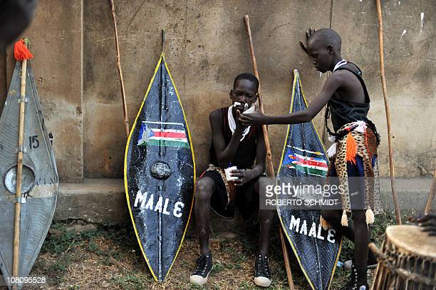 South Sudanese boys belonging to a cultural dance group use moistened ground chalk to mark traditional tribe paintings on their face before their...