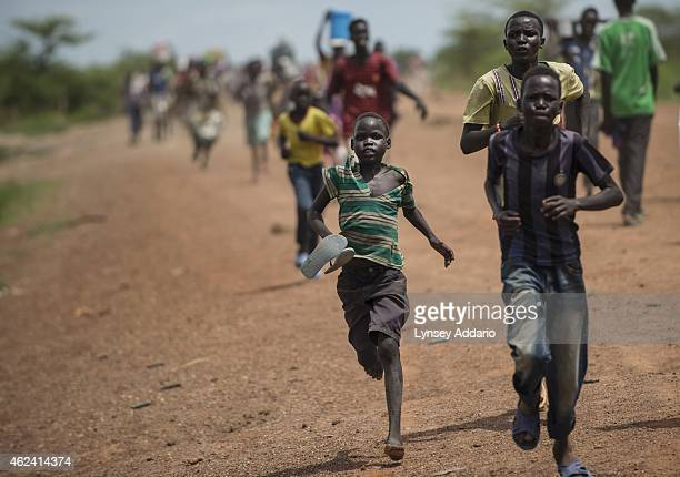South Sudanese children and women run towards the camp for displaced at the United Nations Mission after fearing they saw a government troop in the...