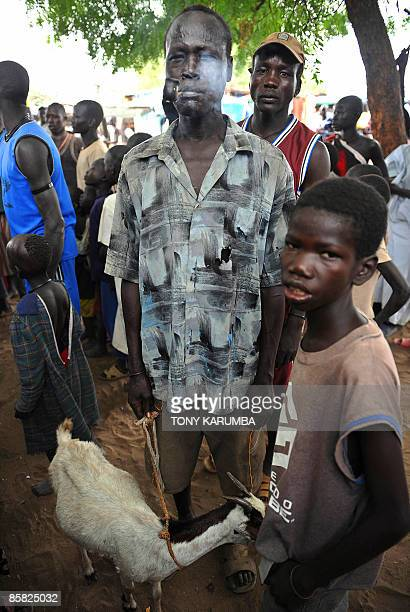 South Sudanese man and youth pose on April 2 at a market at Terekeka, 82 km north of Juba, an area where the population is exposed to malaria, a...