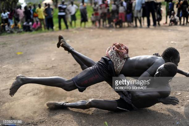 South Sudanese members of the Mundari ethnic group wrestle in a dusty patch where the tribe brought cattle and sheep for sale in Juba on July 7, 2011...