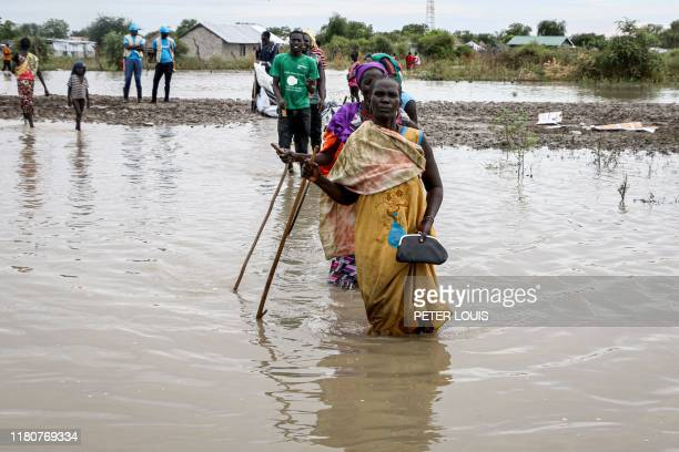 South Sudanese people walk in a flooded area that has been isolated for about a month and half due to the heavy rain in Pibor Town Boma state eastern...