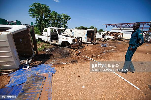 South Sudanese police officer stands guard as he examines on August 18, 2016 the remains of the logistic base of the United Nations organisation...