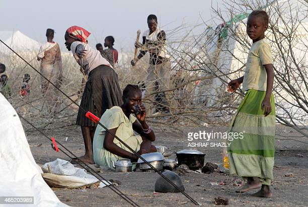 South Sudanese refugee children walk past a woman drinking tea outside a makeshift tent at a camp run by Sudanese Red Crescent where they arrived...