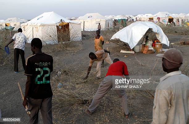 South Sudanese refugee men collect wood near makeshift tents at a camp run by Sudanese Red Crescent where they arrived after fleeing battles between...