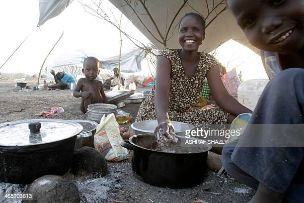 A South Sudanese refugee poses near her children as she cooks at a transitional camp run by Sudanese Red Crescent where she arrived after fleeing...