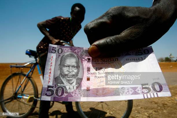 South Sudanese refugee shows his country's fifty-pound note as he flees across the border in Sudan's White Nile state on February 28, 2017. - The UN...