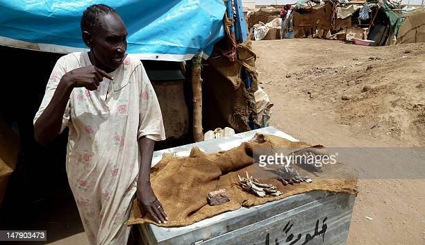 South Sudanese refugee woman sells dried fish at the Dar es Salaam refugee camp in the capital Khartoum on June 28 2012 The Dar es Salaam camp for...