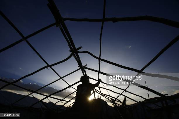 South Sudanese refugees build a hut at the UNHCR camp of alAlgaya in Sudan's White Nile state south of Khartoum on May 17 2017 More than 95000 South...