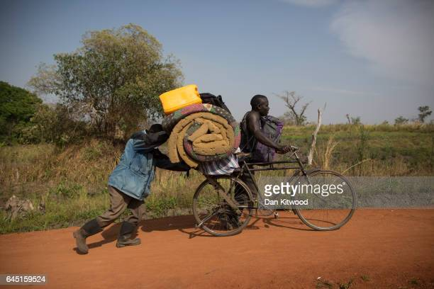 South Sudanese refugees push their belongings up a hill after crossing a small wooden bridge over a river from South Sudan into Uganda on February 24...