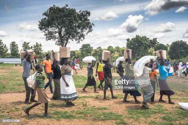 South Sudanese refugees seen taking their food supplies provided by the World Food Program and walk back to their settlement from the food...