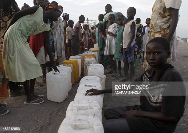 South Sudanese refugees wait to fill jerrycans with water at a camp run by the Sudanese Red Crescent on January 26 2014 in the western part of...