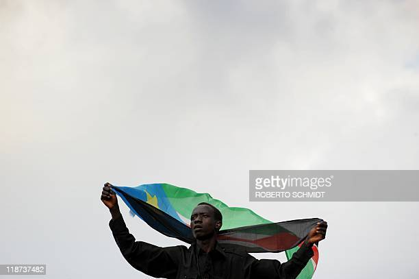 A South Sudanese spectator waves his country's flag as he watches the first international soccer game of the their country's national soccer squad...