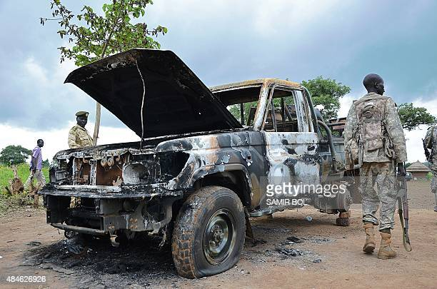South Sudanese SPLA soldiers inspect a burned out car in Pageri in Eastern Equatoria state on August 20, 2015. The spokesman of SPLA, Colonel Philip...