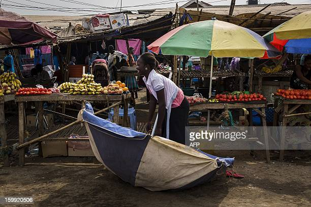 A South Sudanese woman picks up her parasol felled by the wind next to her fruit and vegetables stand at Gudele market in Juba South Sudan January 23...
