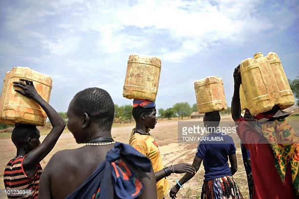 South Sudanese women carry jerry-cans filled with water on their heads on April 2 at Terekeka, 82 km north of Juba, an area where the population is...