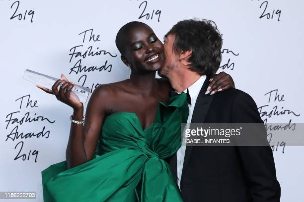 TOPSHOT South SudaneseAustralian model Adut Akech winner of the Model of the Year award poses for a photograph with award presenter Pier Paolo...