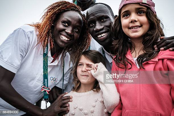 South Sudan's athlete Anjelina Nada Lohalith and James Nyang Chiengjiek for the Refugee Olympic Team take pictures with tourists in front of the...