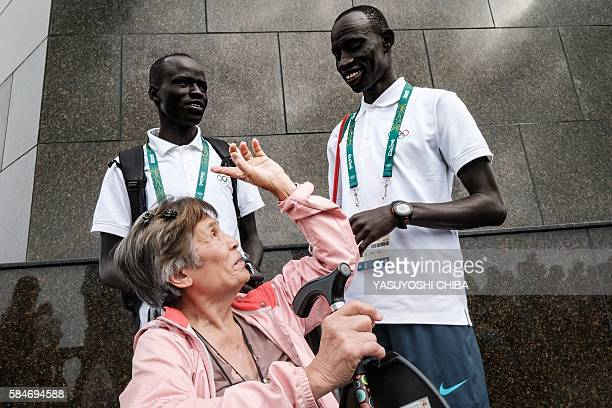 South Sudan's athlete James Nyang Chiengjiek , Yiech Pur Biel based in Kenya for the Refugee Olympic Team talk with a tourist at the statue of Christ...