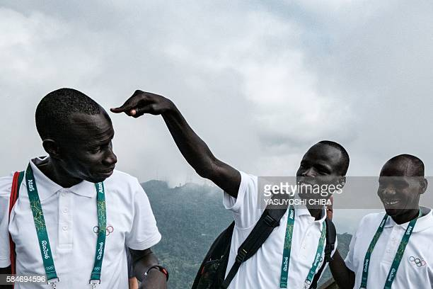 South Sudan's athlete Yiech Pur Biel and James Nyang Chiengjiek based in Kenya for the Refugee Olympic Team joke during a visit to the statue of...