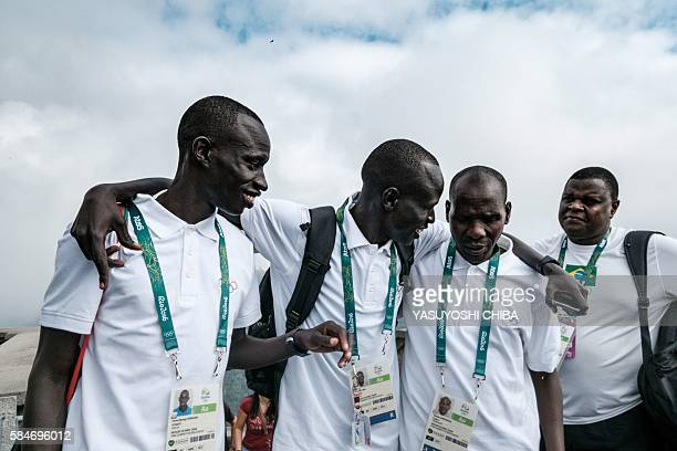 South Sudan's athlete Yiech Pur Biel and James Nyang Chiengjiek based in Kenya for the Refugee Olympic Team speak with Kenyan coach Joseph Domongole...