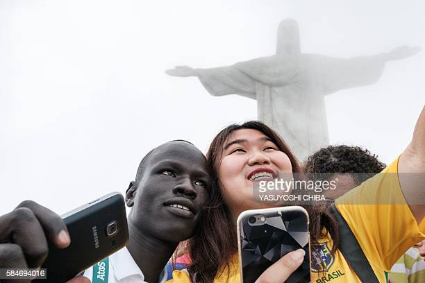 South Sudan's athlete Yiech Pur Biel for the Refugee Olympic Team takes pictures with a tourist in front of the statue of Christ the Redeemer ahead...