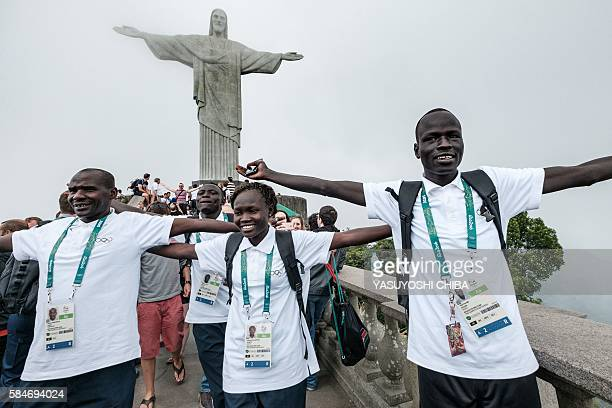South Sudan's athlete Yiech Pur Biel , Rose Nathike Lokonyen based in Kenya, and Kenyan coach Joseph Domongole for the Refugee Olympic Team pose in...