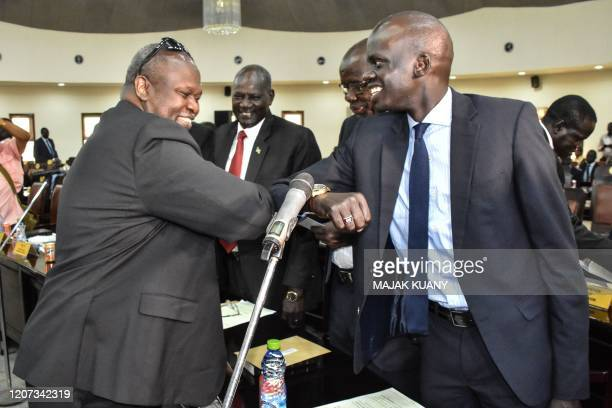 South Sudan's first Vice President Riek Machar greets with the Minister of Petroleum Puot Koang Chol by contacting elbows due to the COVID-19...