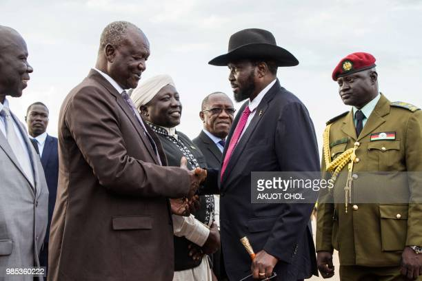 South Sudan's president Salva Kiir and Minster of Defence Kuol Manyang Juuk shake hands as Kiir arrives from Sudan's capital Khartoum at Juba...