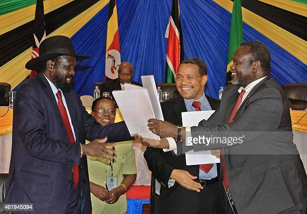 South Sudan's President Salva Kiir exchanges signed documents with South Sudanese rebel leader Riek Machar in northern Tanzania's town of Arusha on...
