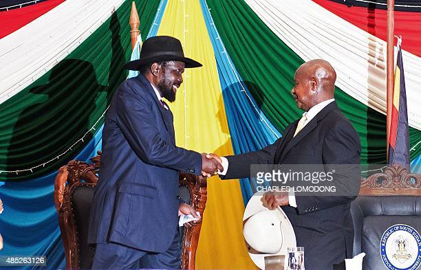 South Sudan's President Salva Kiir shakes hands with Uganda's President Yoweri Museveni after signing a peace agreement in Juba, on August 26, 2015....