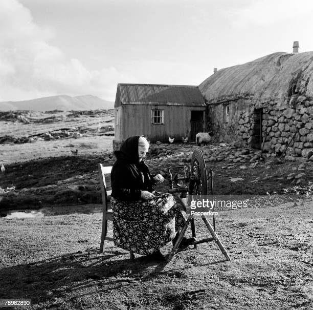 South Uist, Scotland, A crofter sitting at her spinning wheel, In the background is her house or croft