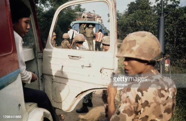 South Vietnam troopers search a truck carrying fleeing refugees, looking for deserting military defenders of the old Imperial capital during the...