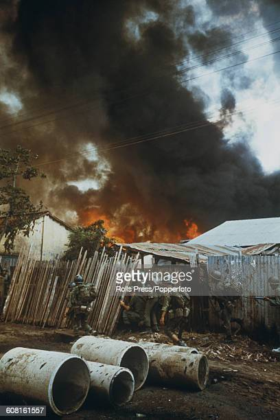 South Vietnamese ARVN Rangers take cover beside a fence as a fire rages amongst buildings behind during fighting in Saigon between South Vietnamese...