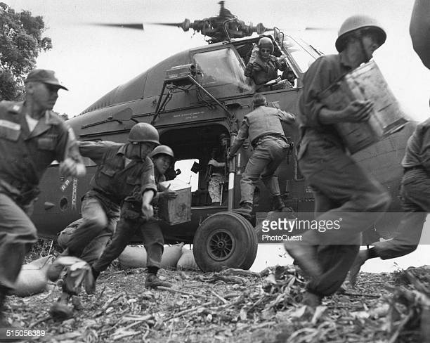 South Vietnamese forces and American advisors under attack by Viet Cong guerillas in jungle clearing as supplies from United States helicopter are...