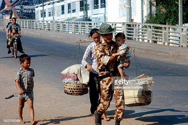 A South Vietnamese officer flees with his family the woman carries their possessions in baskets Saigon 1968