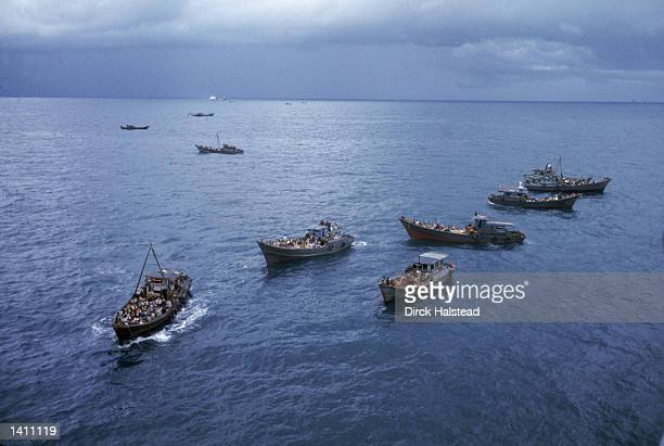 South Vietnamese refugees in boats approach a U.S. War ship to seek refuge from the invading force from the North April 1975 in the South China Sea...