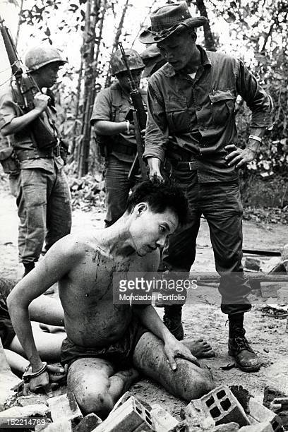 A South Vietnamese soldier displays an injured halfnaked Viet Cong pulled out of a crater after the explosion of a mine and taken prisoner Vietnam...