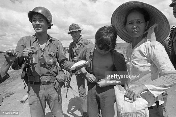 South Vietnamese soldier holding the fake identity papers of a teenage Vietcong suspect caught after he tried to escape from an Hoa village on...