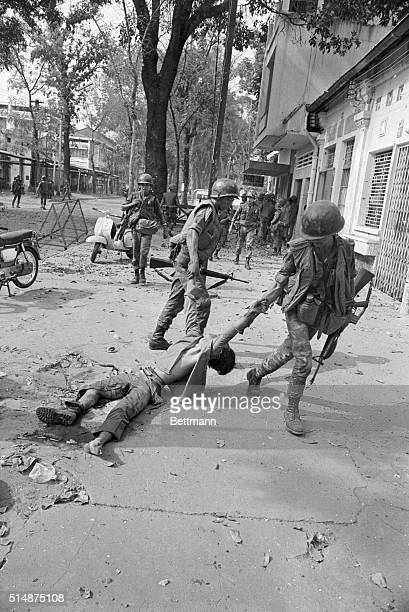 South Vietnamese soldiers drag the body of a dead Vietcong guerrilla away from a government building during a rash of Vietcong attacks in Saigon...
