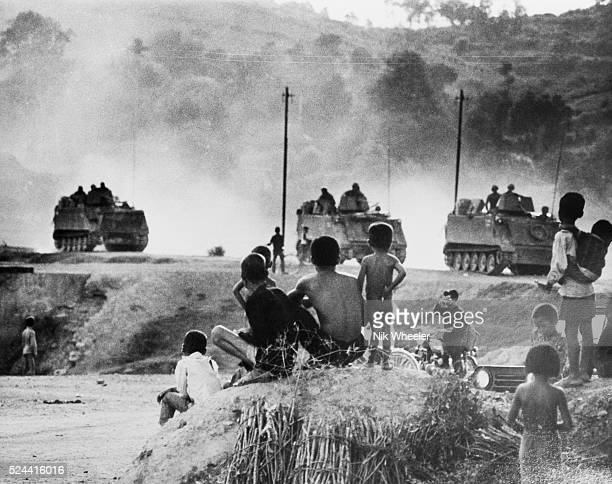 South Vietnamese villagers pause to watch a convoy of US Army armored personnel carriers kick up dust as they drive along a dirt road near Saigon...