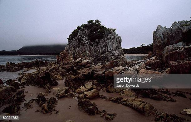 Stormy skies over a granite outcrop exposed at low tide.
