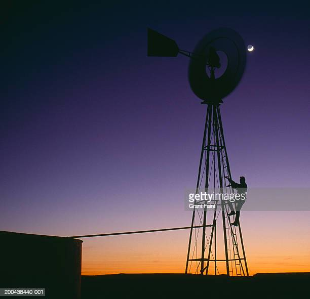usa, south west, silhouette of man climbing windmill, dusk - american style windmill stock pictures, royalty-free photos & images